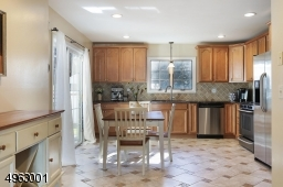 a spacious kitchen with high end stainless steel appliances, granite countertops, wood cabinetry, and breakfast area
