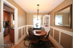 Inviting Dining Room features built-in corner cabinet and custom wainscoting