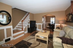 View of Living Room and staircase leading to 2nd floor.  Hardwood floors in LR, DR, staircase
