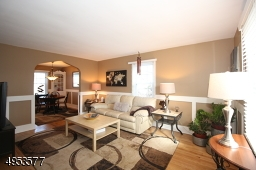Living room features custom wainscotng, wood floors, and arched entryway to formal Dining Room