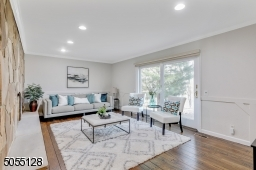 Family Room with recessed lights, elaborate woodwork on walls, chair rail and glass sliders to brick patio and double privacy doors to hallway