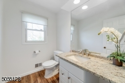 Powder Room with hardwood floors, white vanity with granite top and recessed lights.