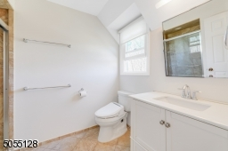 Primary Bathroom features stone floors, white vanity, glass enclosed frames walk-in shower with recessed light and linen closet.