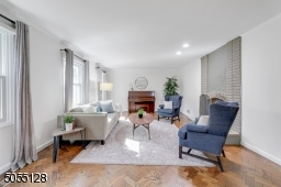 Living Room features deep baseboard moldings, crown moldings, chevron wood floors, recessed lights, 3 windows and floor-to-ceiling brick fireplace (wood burning)