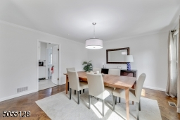 Dining Room with deep baseboard moldings, crown moldings, 2 windows and barrel chandelier