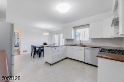 Gourmet Chef?s Eat-In Kitchen features crisp white wood custom cabinetry, quartz counters, textured tile backsplashes, stone floors, coffee bar with glass shelves.