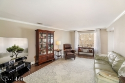 Enjoy the woodland and pond views from this roomy living room with crown molding and engineered hardwood flooring.