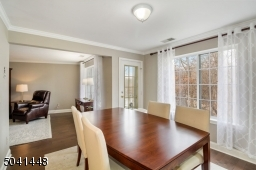 Inviting Dining Room with picture window overlooking woodland/pond views and balcony access.
