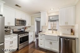 Renovated in 2019! Features include crisp white cabinetry, classic farm sink, brass hardware & faucet, gleaming quartz countertops and engineered hardwood flooring!