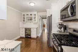 Attractive bar area with built-in beverage refrigerator, wine rack, glass display cabinetry and quartz countertops.