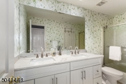 Main full bath sports a new white double vanity with lovely quartz countertops, and a new commode.