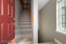 Entry view with new wall-to-wall carpeting on stairs that lead up to main level and down to lower level bonus room with newer full bath and direct garage access.