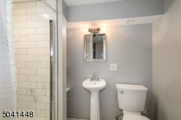 Newer full bath on lower level has Carrera marble subway-tiled stall shower and flooring.