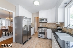This delightful eat in kitchen featuring top-notch stainless steel appliances and custom cabinetry is a great space for prepping meals while keeping an eye on the little ones in the fenced in back yard.