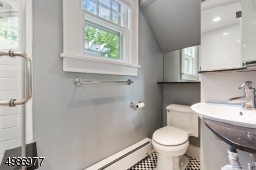 First floor bath features steam shower with frameless glass doors, marble seat, black and white checked floor tiles and electric baseboard heat.