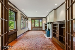 Elegant front family/gathering room features stately fireplace flanked by built-in bookcases, natural wood trim, oak wood flooring and recessed lighting.