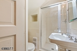 Secondary upper level full bath features pedestal sink, subway tiled stall shower, hexagonal tile flooring and skylight.