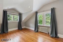 Bedroom features oak wood flooring and recessed lighting.