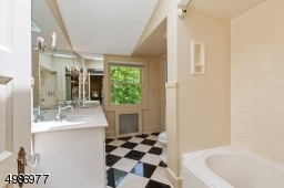 Master bath features double vanity with marble countertop, tiled shower over tub, beadboard wainscoting, skylight and black and white marble tile floor.