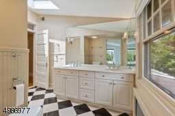 Custom white cabinetry, high-end faucets and two entry doors lead to the hall and master bedroom.