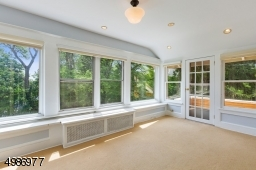 Master sitting room features walls of windows and frech door leading to upper level balcony.