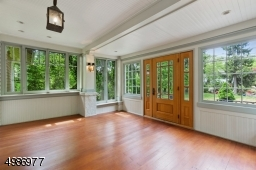 Elegant enclosed heated front porch with cedar floor, beadboard ceiling, recessed lighting and cedar floor.