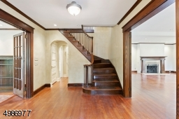 Grand foyer with beautiful wood turned staircase and double french doors leading to the living and family rooms.