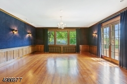 Banquet sized dining room features natural wood panel wainscoting, French doors to outdoor patio, recessed lighting, wall sconces and swing door access to kitchen/butler's pantry.