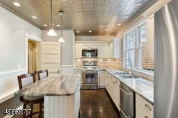Chef's kitchen with beadboard cabinets, granite countertops, subway tiled backsplash, tin ceiling, and wide plank wood floors.