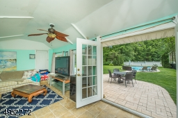 With a view from the comfortable Pool House over the Patio towards the in-ground, heated Pool