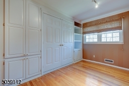 With custom wall including a murphy bed, craft table and bookshelves.