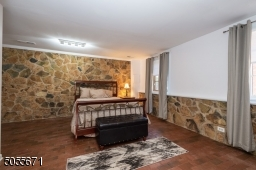 """See the amazing stone walls and floors in the bedroom of the garden suite.  This is not """"underground"""" as you can tell by the abundance of full size windows."""