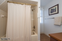 Full ceramic tile tub shower in a neutral beige