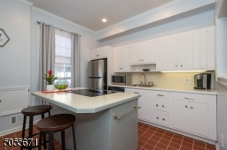 Fresh white cabinets with pale grey blue walls.  Island has drop in electric range and oven (out of view).  Dishwasher is right of stainless refrigerator.