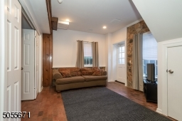 """This is such a cool area.  At the bottom of the staircase is a whole other world.  We are looking at the """"den"""" or sitting area portion of the suite.  Note all the light and the door to the (small) outdoor patio.  Perfect for work-from-home."""
