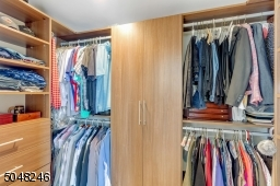 This large walk in closet has a new California Closet custom system installed.