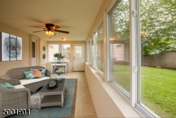 Enclosed Porch with walls of windows and tiled floors.