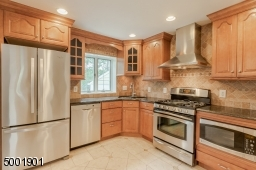 """Updated kitchen w/marble floor, lovely custom 42"""" cabinets, granite countertop, tiled back splash and stainless steel appliances."""