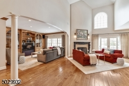 The expansive great room with it's impressive 20' 2-story ceiling, gas fire place, Bertch custom cabinetry with wet bar, wine refrigerator and wide plank wood floor is a terrific entertaining space.
