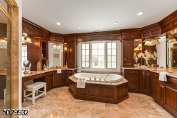 Bathroom with marble shower, countertops, and floor, 2 vanities, 2 sinks and custom cabinetry.