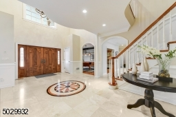 Grand 2-story entrance with 18' ceiling, marble floor, crystal chandelier, 2 coat closets, custom millwork, arched doorways, pillars, and curved staircase.