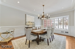 Sun-filled dining room with beautiful moldings, bay window, arched doorway, hardwood floor and swing door to kitchen.