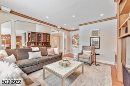 Wide plank wood floor, pillars, custom built-in book shelves & cabinetry with surround sound speakers.