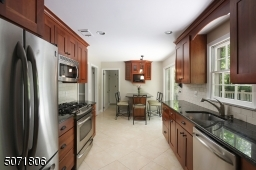Granite counters, wood cabinets, stainless steel appliances and outdoor access.