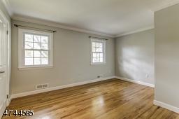 Spacious bedroom, wood floor, closet.