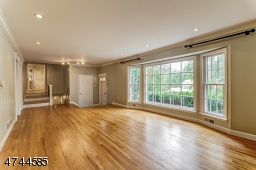 Spacious Living Room with large picture window, wood floor, recessed lighting.