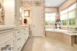 Upscale cabinetry, sinks, and faucets complement the large glass enclosed shower and soaking tub.