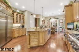 The kitchen features a new Sub-zero refrigerator (2018) and GE Monogram appliances, including Island microwave, warming drawer, and wet bar sink with water filtration system.