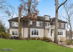 Covered front entry with Mahogany front door with decorative metal hardware featuring bead board ceiling with flush mount lantern with glass windows surrounded by sidelights and transom windows.