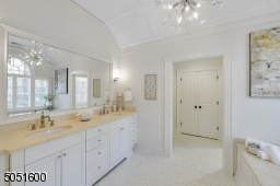 Primary Bathroom w/ tile floors w/ radiant heat, vaulted tray ceiling, chandelier, oversized walk-in shower, w/ marble & glass tile surround, soaking tub, baseboard molding, recessed lighting, dual custom vanities dual designer sconces & built-in speaker